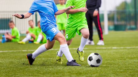 football teams: Boys Kicking Football Ball on Sports Field. Soccer Game for Youth Teams. Stock Photo