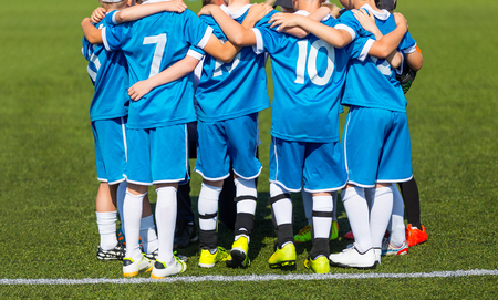 Kids with soccer coach gathering before match. Youth soccer football team. Group photo. Soccer players standing together united. Soccer team huddle. Teamwork, team spirit and teammate example. Stock Photo