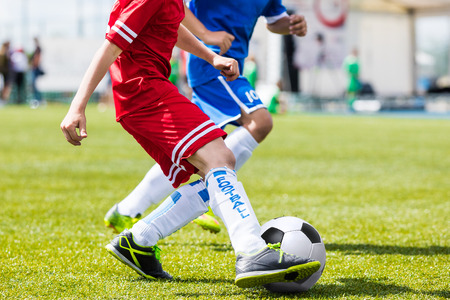 footwork: Boys kicking soccer ball. Footballer dribbling and kicking ball. Soccer players kicking ball on sports field. Competition game between youth football teams.