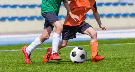 green grass: Young boys children in uniforms playing youth soccer football game tournament. Horizontal sport background.
