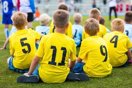 terrain de handball: équipe de football Les enfants de football au stade de sport. Les garçons assis sur un terrain de football lors du tournoi de football de l'école