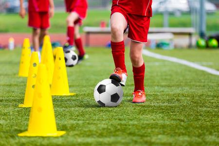 Fotbollsfotbollsspelare under lagträning före matchen. Övningar för fotbolls-fotbolls ungdomslag. Ung spelare övningar med boll och markörskeglar