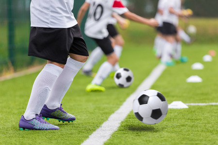 sports club: Football soccer training for youth teams. Young footballers kicking soccer balls