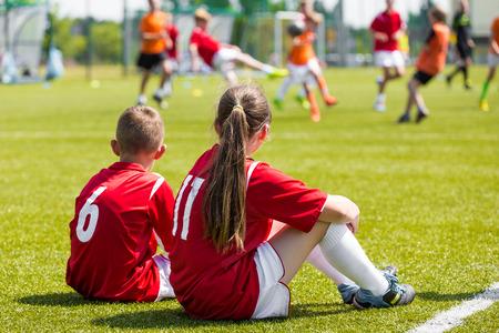 Niños jugadores de fútbol que juegan al juego. Los jóvenes jugadores de fútbol niña y niño sentados juntos en el campo de fútbol de hierba Foto de archivo - 64613943