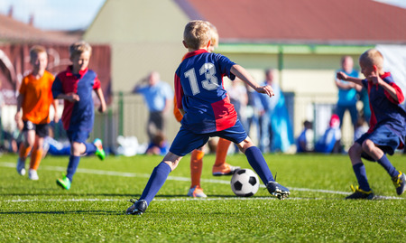 football play: Boys Play Football; Children kicking Soccer Ball; Football Tournament for Youth Sports Teams
