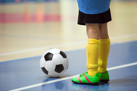 futsal: Football futsal training for children. Indoor soccer young player with a soccer ball in a sports hall. Player in blue and yellow uniform. Sport background.