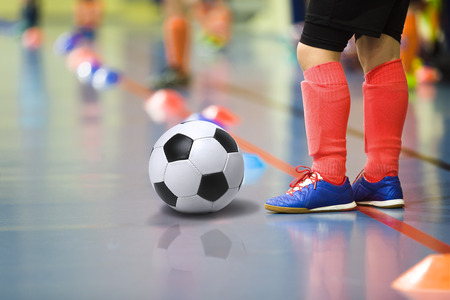 Children training soccer futsal indoor gym. Young boy with soccer ball training indoor football. Little player in light red sports socks