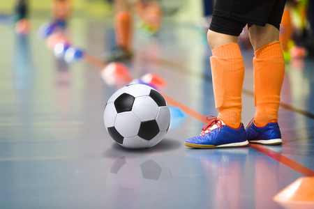 Children training soccer futsal indoor gym. Young boy with soccer ball training indoor football. Little player in light orange sports socks