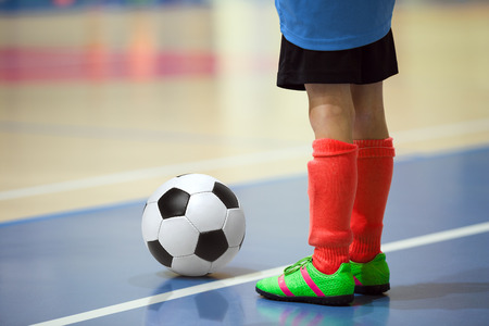 futsal: Football futsal training for children. Indoor soccer young player with a soccer ball in a sports hall. Player in blue and red uniform. Sport background.