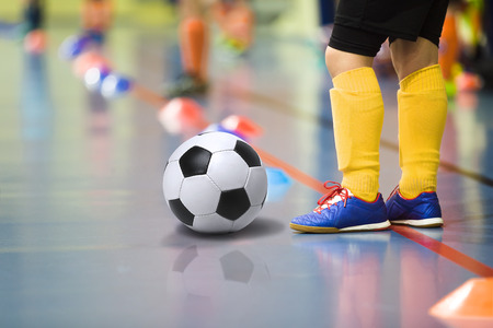 futsal: Children training soccer futsal indoor gym. Young boy with soccer ball training indoor football. Little player in yellow sports socks Stock Photo