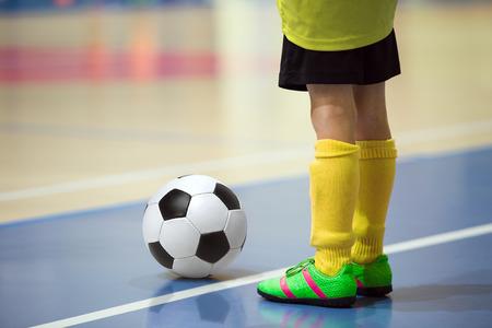 Voetbal futsal training voor kinderen. Zaalvoetbal jonge speler met een voetbal in een sporthal. Speler in het geel uniform. Sport achtergrond. Stockfoto