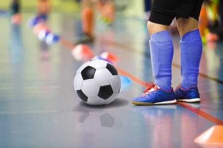 futsal: Children training soccer futsal indoor gym. Young boy with soccer ball training indoor football. Little player in dark blue sports socks Stock Photo