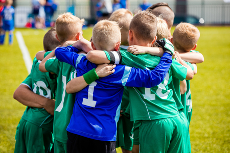 Young football soccer players in sportswear. Young sports team with football coach. Pep talk with coach before the final match. Soccer school tournament Stock Photo