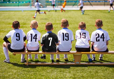 Piłkarze o meczu gry. Młoda Soccer Team siedzi na drewnianej ławce. Mecz piłki nożnej dla dzieci. Chłopcy Odtwarzanie turnieju piłki nożnej meczu. Piłkarze młodzieżowe klub piłkarski Zdjęcie Seryjne