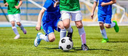 Laufen Fußball Football-Spieler. Fußballspieler kicking Fußball-Spiel-Spiel. Junge Fußball-Spieler nach dem Ball laufen. Fußball-Stadion im Hintergrund