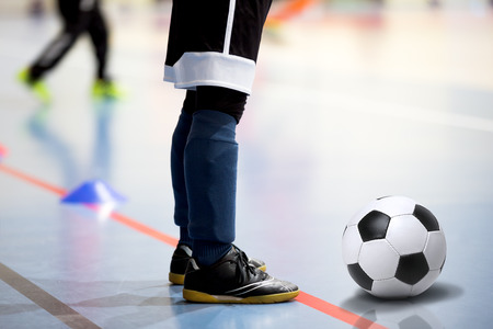 halls: Football futsal training session. Futsal player with soccer ball. Indoor soccer young player with a soccer ball in a sports hall. Sport background.
