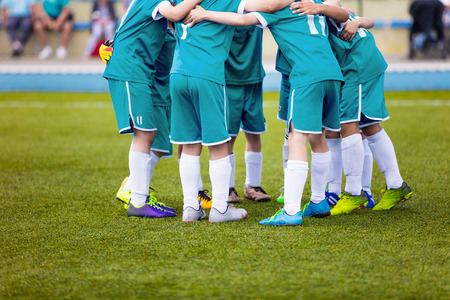 Young football soccer players in aquamarine sportswear. Young sports team on pitch. Pep talk before the final match. Soccer school tournament. Children on sports field.