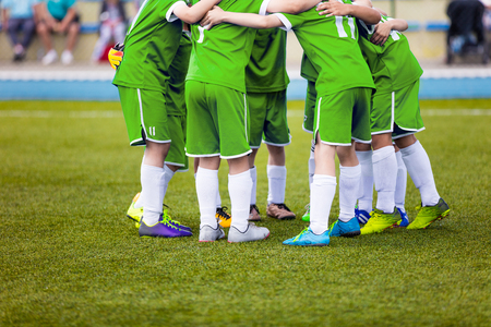 pep: Young football soccer players in green sportswear. Young sports team on pitch. Pep talk before the final match. Soccer school tournament. Children on sports field.