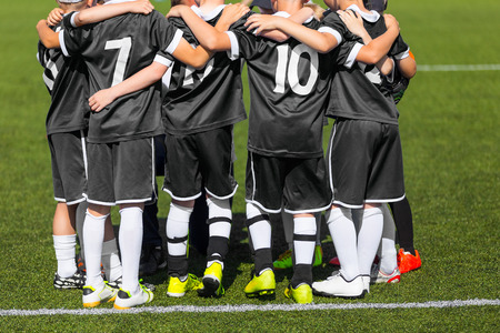 talent: Young football soccer players in black sportswear. Young sports team with football coach. Pep talk with coach before the final match. Soccer school tournament