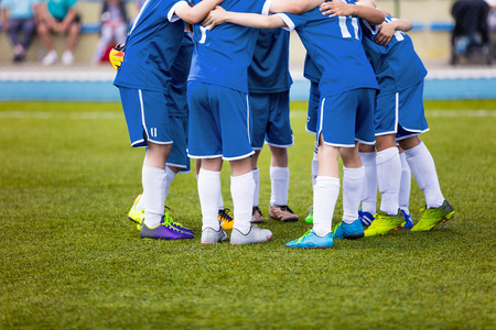 Young football soccer players in blue sportswear. Young sports team on pitch. Pep talk before the final match. Soccer school tournament. Children on sports field. Stock Photo