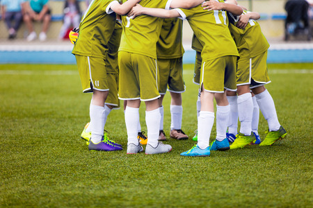 pep: Young football soccer players in yellow sportswear. Young sports team on pitch. Pep talk before the final match. Soccer school tournament. Children on sports field. Stock Photo