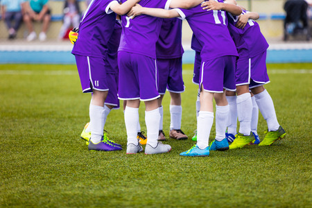 pep: Young football soccer players in purple sportswear. Young sports team on pitch. Pep talk before the final match. Soccer school tournament. Children on sports field.