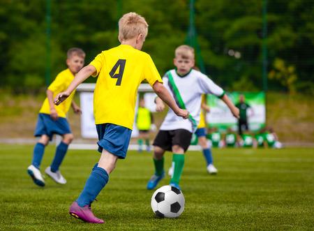 jugadores de futbol: Muchachos que golpea el balón de fútbol. Los niños del equipo de fútbol. Cabritos que se ejecutan con la bola en Campo de fútbol. Jóvenes futbolistas en Acción Foto de archivo