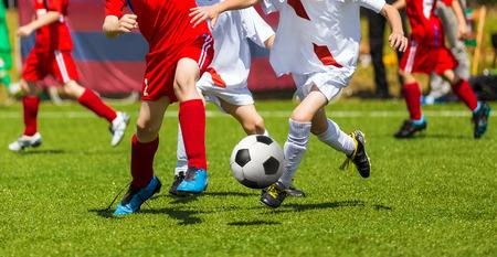zapatos escolares: Kick Fútbol fútbol. Jugadores de fútbol duelo. Chidren que juegan a fútbol juego de fútbol en campo de deportes. Chicos jugar partido de fútbol en la hierba verde. Jóvenes equipos de competición torneo de fútbol Foto de archivo