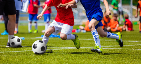 sports training: Football Soccer Match for Children. Kids Playing Soccer Game Tournament. Boys Running and Kicking Football. Youth Soccer Coach in the Background Stock Photo