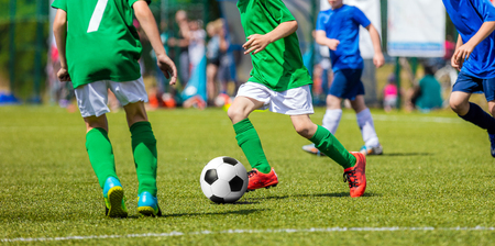 Children Soccer Players Running with the Ball. Kids in Blue and Green Soccer Jerseys Playing Football on the Pitch. Sports Stadium in the Background