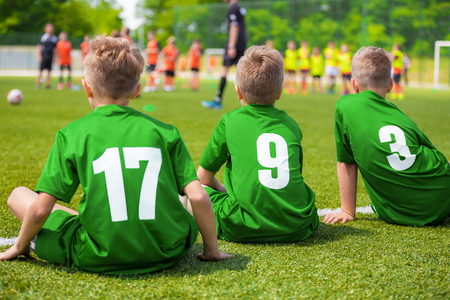 Kids Soccer Players Sitting on the Pitch. Young Boys of Football Team Sitting on Green Grass.