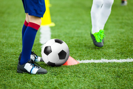 Children Football Soccer Training. Young Athlete with Football Ball on Pitch. Kids in Soccer Uniform Kicking Ball. Boy Practice Dribbling Drills on Sport Grass Field