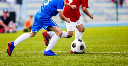 Voetbalwedstrijd voor kinderen. Kinderen voetballen toernooispel. Jongens rennen en schoppen voetbal op het sportveld. Twee jeugdvoetbalspelers strijden om het voetbal