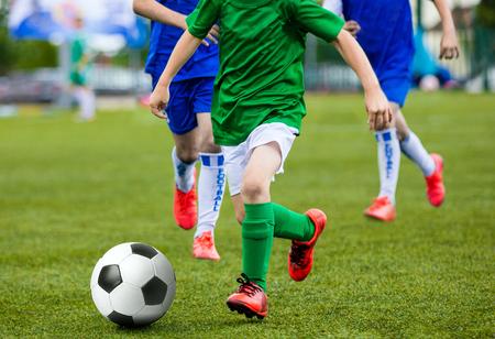 pelota de futbol: Young Boys Kids Children Playing Football Soccer Game. Running Soccer Players in Green and Blue Uniforms. Boys Kicking Soccer Ball