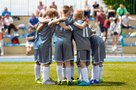 Childrens Football Team on the Pitch. Boys in Grey Soccer Jersey Shirts Standing Together on the Football Field. Motivated Young Soccer Players Before the Final Game of School Tournament Stock Photo