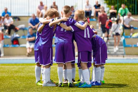Kindervoetbalteam op het veld. Jongens in Purple Soccer Jersey Shirts Staan samen op het voetbalveld. Gemotiveerde jonge voetballers voor het laatste spel van het schooltoernooi