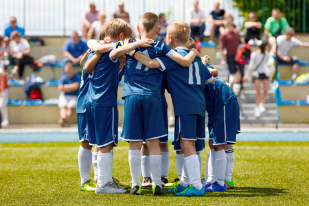 Childrens Football Team on the Pitch. Boys in Blue Soccer Kits Standing Together on the Football Field. Motivated Young Soccer Players Before the Final Game of School Tournament Stock Photo
