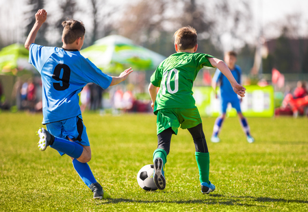 Kids kicking soccer ball on vivid green grass field. Soccer pitch in the background. Football soccer background. Football league game Stock Photo