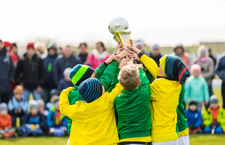 Young Soccer Players Holding Trophy. Boys Celebrating Soccer Football Championship. Winning Youth Team of Sport Tournament for Kids Children. Children as Sports Champions Stock Photo