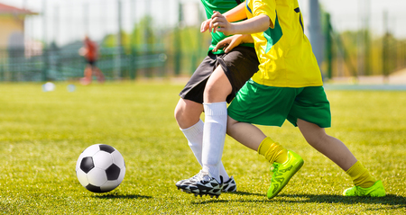 Training and football match between youth soccer teams. Young boys playing soccer game. Hard competition between players running and kicking soccer ball. Final game of football tournament for kids. Stock Photo