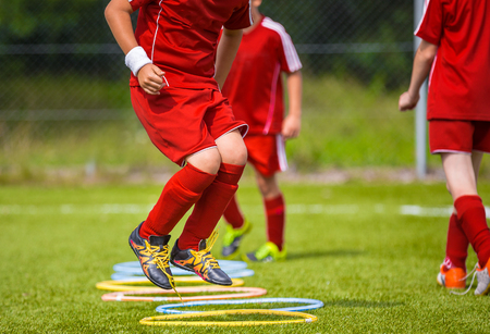 Young Soccer Player Practicing on the Pitch. Soccer Football Equpment. Dynamic Jumping Football Training