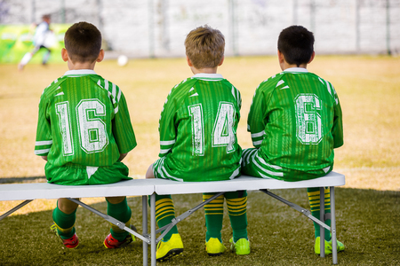 Kids Soccer Team. Young Boys Reserve Players Sitting on Bench and Watching Youth Soccer Match. School Football Soccer Game Stock Photo