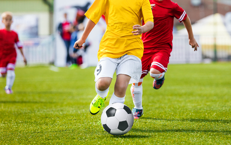 Running Youth Soccer Football Players. Boys Kicking Soccer Match. Children Football Players Running After the Ball. Kids Sport Duel Stock Photo