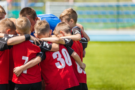 Children sports soccer team. Kids standing together on the football pitch. Soccer coach motivational team talk. Youth football soccer coach motivating players before match. Stok Fotoğraf - 82311407