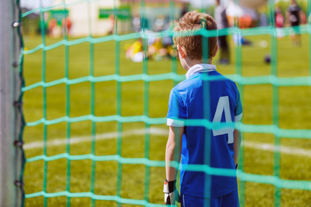 Young boy as a soccer goalkeeper during football match ready to save