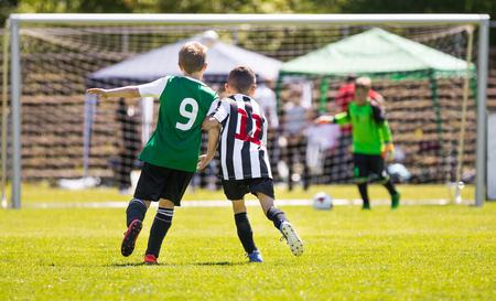 Running Youth Soccer Football Players. Boys Kicking Soccer Match. Children Football Players Running After the Ball. Kids Sport Duel Lizenzfreie Bilder