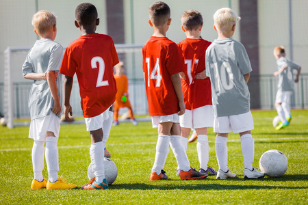 Boys Play Soccer Training Match. Children Sport Team. Youth Sports Team Together. Football Soccer Game For Children. Kids Soccer Players on bench Watching Tournament Game. Penalty Game in the Background