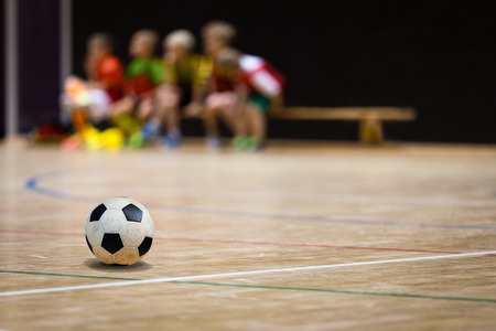 Football Futsal Ball and Youth Team. Indoor Soccer Sports Hall. Children Indoor Soccer Team. Sport Futsal background. Indoor Soccer Winter League for Kids