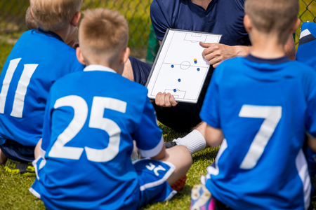 Coaching Kids Soccer. Football Team with Coach at the Stadium. Boys Listening to Coachs Instructions Before Competition. Coach Giving Team Talk Using Soccer Tactics Board