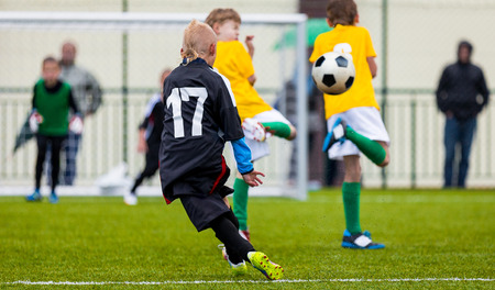 Soccer Football Match. Single Player Kick off. Kids Playing Soccer. Young Boys Kicking Football Ball on the Sports Field. Kids Playing Soccer Tournament Game on the Pitch. Youth European Football Match Stock Photo